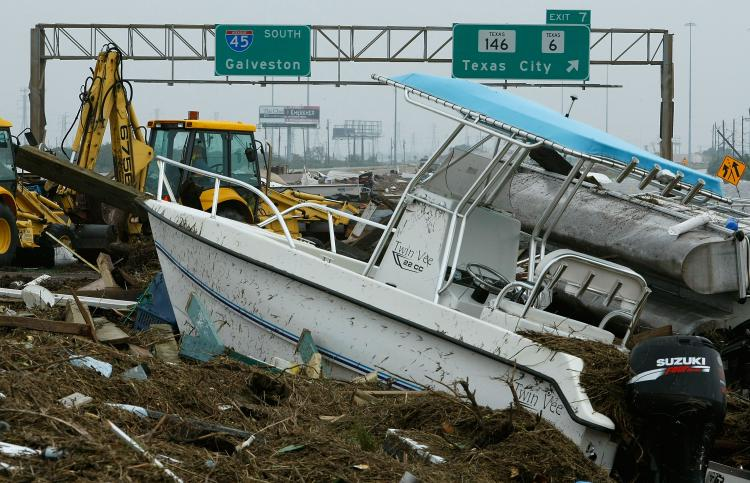 IKE AFTERMATH: Heavy equipment starts to move boats and other debris off of Rt.45 left by Hurricane Ike September 13, 2008 in Galveston, Texas. Hurricane Ike made landfall in the middle of the night causing wide spread damage to the Texas coast.  (Mark Wilson/Getty Images )