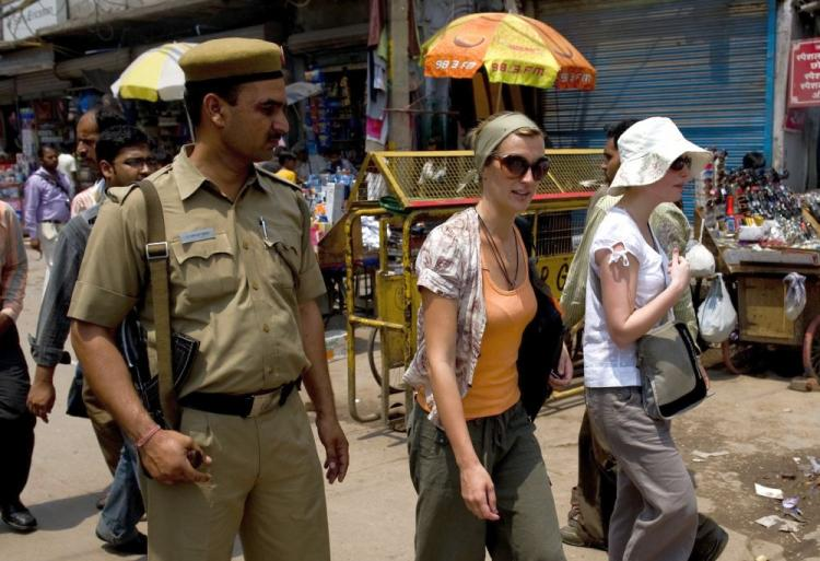 Foreign tourists are watched by an Indian policeman as they walk along a street in New Delhi on May 2. Thousands of Indian police and paramilitary troops are guarding New Delhi's markets and shopping centers after a series of warnings from foreign embassies of an imminent militant attack. (Manpreet Romana/AFP/Getty Images)
