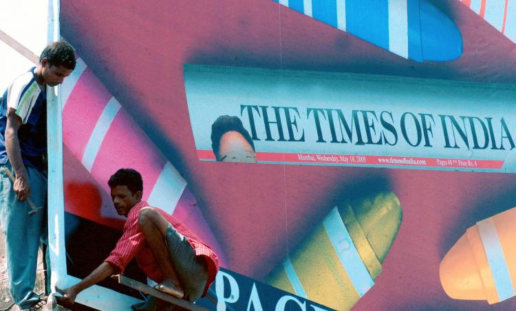 Indian workers puting up a billboard advertising a newspaper on 19 May 2005 in Mumbai. (Indranil Mukherjee/AFP/Getty Images)