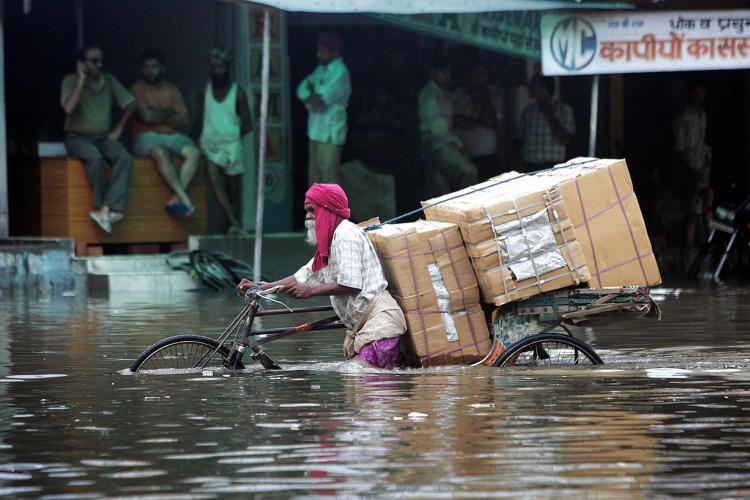 Indian commuters make their way through a waterlogged street after a heavy downpour flooded parts of Amritsar on August 13, 2008.  (Narinder Nanu/AFP/Getty Images)