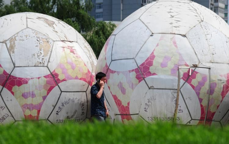 A man on his cell phone walks past giant footballs in Beijing on June 23, 2010. Though gambling is outlawed in China, it has not stopped a thriving underground industry, which manifested in gambling syndicates and online betting during the World Cup.  (Frederic J. Brown/AFP/Getty Images)