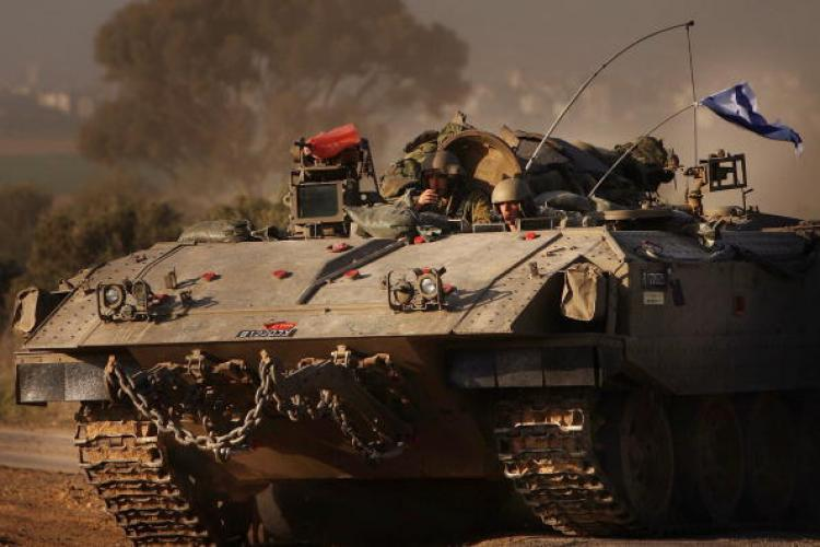 Israeli soldiers ride in a armored personnel carrier (APC) along the Israeli, Gaza border in Israel.  (Spencer Platt/Getty Image)