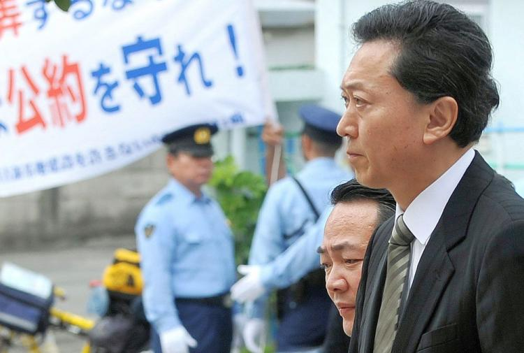 Japanese Prime Minister Yukio Hatoyama walks past a banner which reads 'Keep the pledge!' in Naha, Okinawa Prefecture, after his meeting with Okinawa Governor Hirokazu Nakaima and 12 mayors on May 23. Hatoyama apologized for breaking his election pledge to move an unpopular US military base off Okinawa. (Jiji Press/AFP/Getty Images)