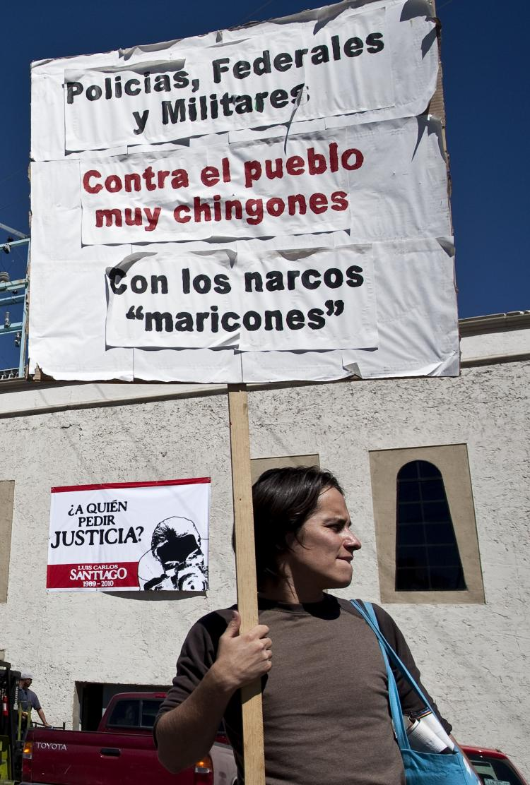 A man holds a sign in Ciudad Juarez, known as Mexico's murder capital, in front of El Diario de Juarez newspaper on Oct. 12, 2010, during a protest against the murder of 21-year-old photojournalist Luis Carlos Santiago, who worked for the newspaper. (Jesus Alcazar/AFP/Getty Images)