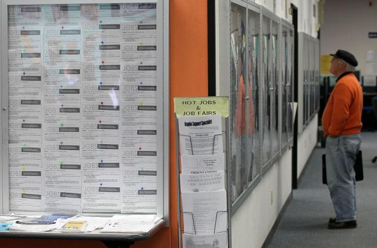 A job seeker looks at job listings posted on bulletin boards in San Francisco, California. Flexible employment and temporary employment are on the rise. (Justin Sullivan/Getty Images)