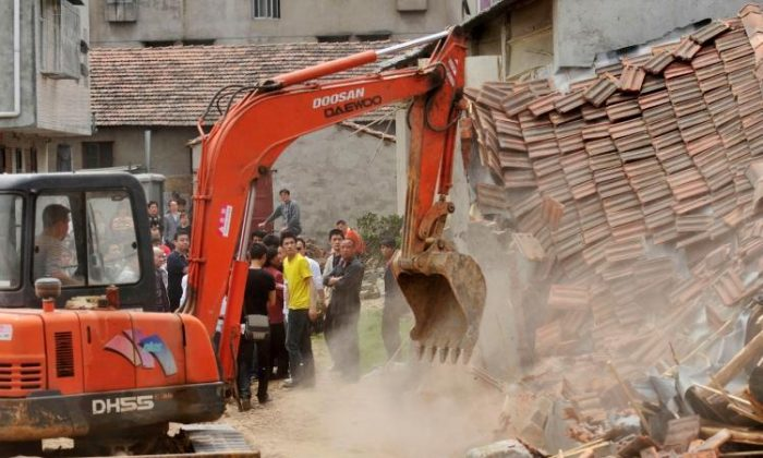 Chinese authorities demolish houses, which are claimed to be illegal by the local government in Wuhan, central China's Hubei Province, on May 7, 2010. (STR/AFP/Getty Images))