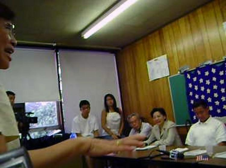 New York Councilman John Liu (right) plays with his cell phone while Taiwanese American Mr. Wang Suhua speaks at the August 18 meeting. (The Epoch Times)