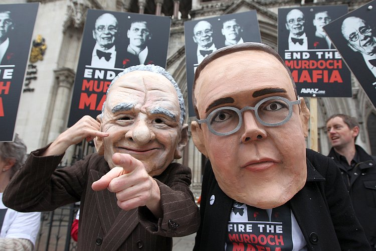 Protesters wearing large Rupert and James Murdoch masks