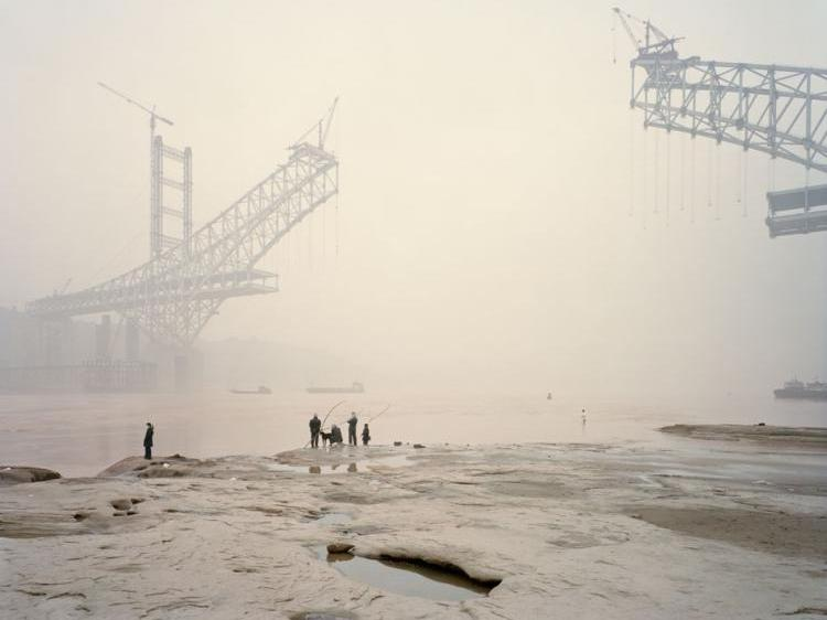 An image in Nadav Kander's book 'Yangtze-The Long River,' of the Chaotianmen Bridge, the world's longest arched bridge, being built over China's Yangtze river. (Courtesy of Hatje Cantz)