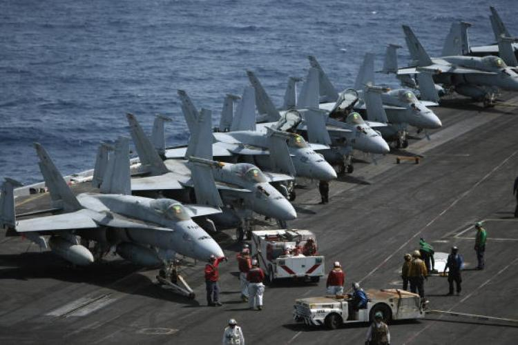 US Navy Advancement Test Results Arrive Today. In this image, US Navy crewmen gather around a line of F-18 jet fighters on the deck of the USS Eisenhower aircraft carrier in the Arabian sea on May 24. (Marwan Naamani/AFP/Getty Images)