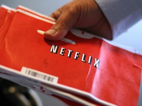 A U.S. Postal worker holds a stack of Netflix envelopes