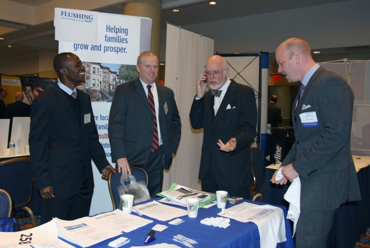 NETWORKING: Flushing Bank representatives discuss mortgages, purchasing, and refinancing of properties. Bankers rubbed shoulders with brokers at the NYC Real Estate Expo (Tara MacIsaac/The Epoch Times)