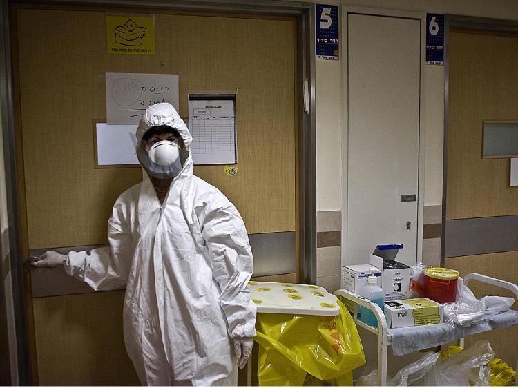 An Israeli nurse at the Tel Aviv Medical Centre prepares to enter the isolated room of a man diagnosed with swine flu in Tel Aviv. (Jonathan Nackstrand/AFP/Getty Images)