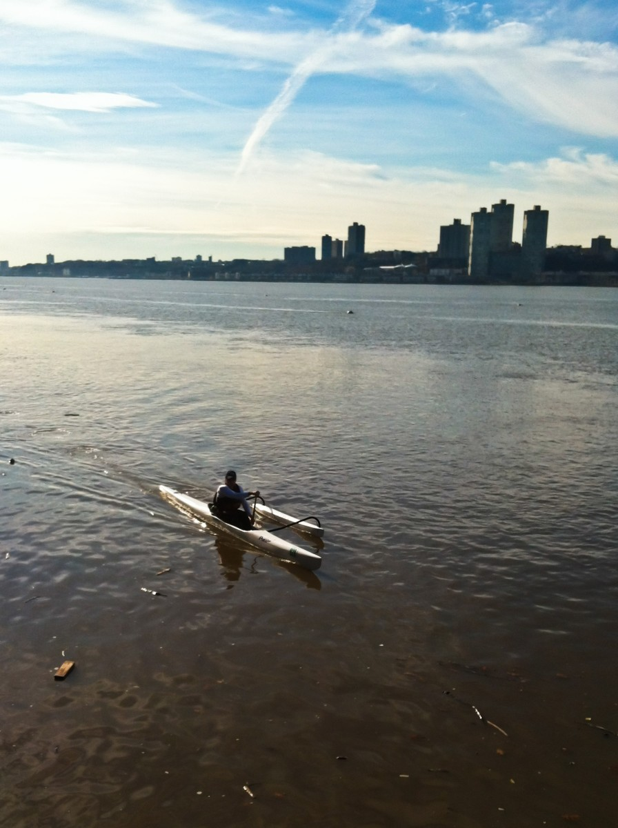 An outrigger canoe paddler heads down the Hudson River during the summer. (Charlotte Cuthbertson/The Epoch Times)