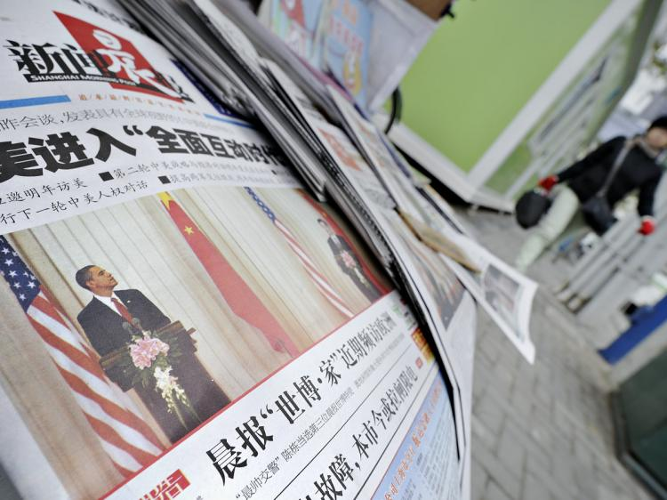 A woman (R) walks past a news stand in Shanghai where Chinese newspapers reporting US President Barack Obama's visit to China are displayed on November 18, 2009. (Philippe Lopez/AFP/Getty Images)