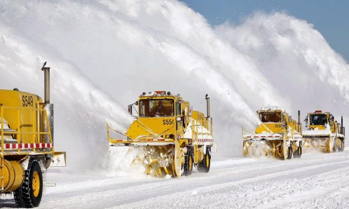 Workers remove snow from a runway at O'Hare International Airport in Chicago on Feb. 3, 2015. (Scott Olson/Getty Images)