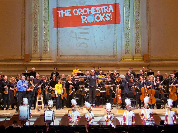 ROCKIN': Conductor Rossen Milanov stands center after 'The Orchestra Rocks' performance with host Thomas Cabaniss (L) where school kids celebrated LinkUp! Program's 25th anniversary. (Kristina Skorbach/The Epoch Times)
