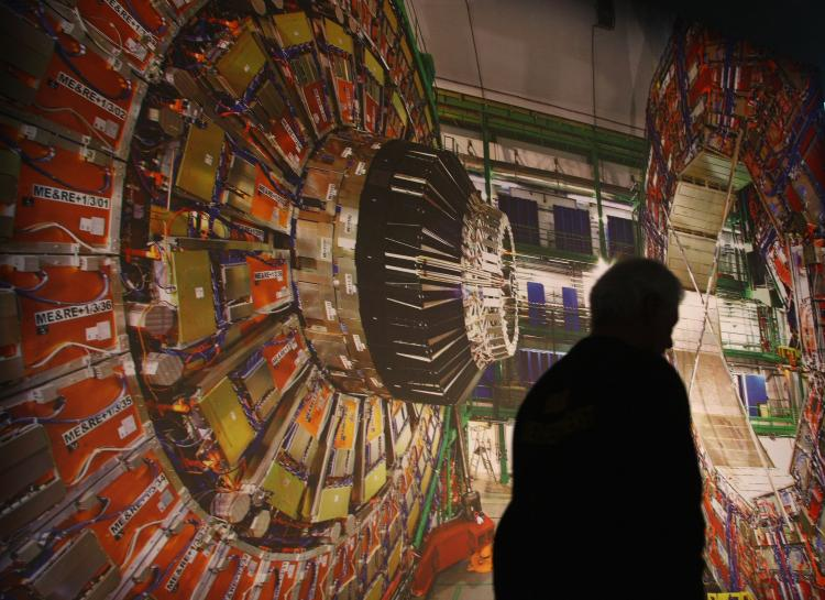 A worker walks past a giant photograph of one part of the Large Hadron Collider, called the 'CMS detector.' (Sean Gallup/Getty Images)
