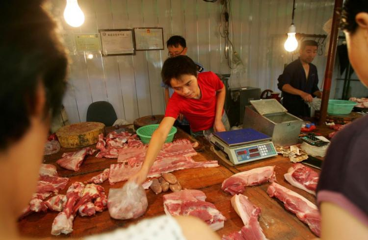 A vendor sells pork at a meat market in Xian of Shaanxi Province, China. A large-scale outbreak of hog cholera in  Zhejiang Province over the past two months has been ignored by officials, say locals. (China Photos/Getty Images)