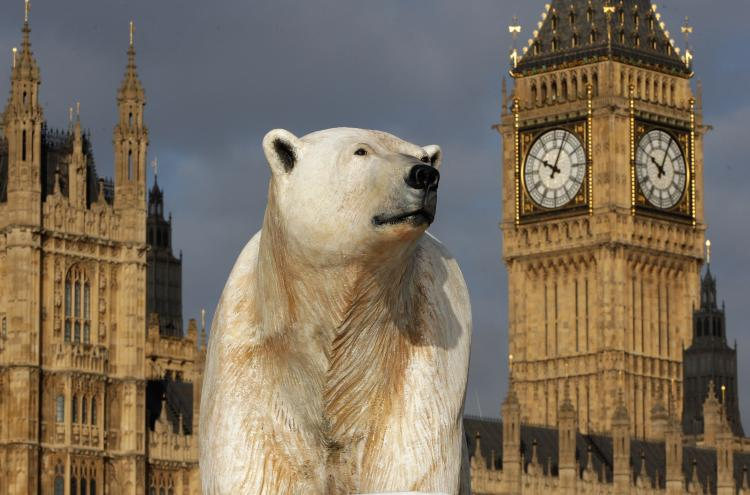 A 16-foot-high sculpture of a polar bear and cub, afloat on a small iceberg, passes in front of the Houses of Parliament on the River Thames in London, January 2009. (Oli Scarff/Getty Images)