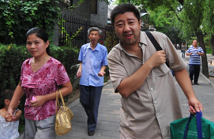 Hai Mingyu (2nd R) walks through a Beijing park chased by plainclothes security personnel (R) despite the Chinese government's promises to allow protests. (Frederic J. Brown/Getty Images)