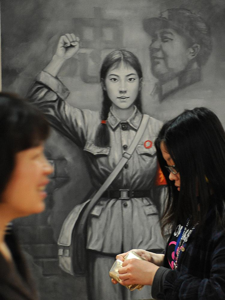 Two Chinese women walk past a painting of a Red Guard from China's Cultural Revolution period at an art exhibit in Shanghai on April 17, 2008. (Mark Ralston/AFP/Getty Images)