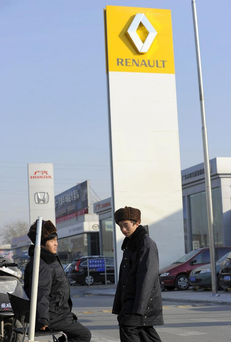 ESPIONAGE: Two security men are on duty next to a sign displaying the logo of French automaker Renault SA at a dealership in Beijing on Jan. 10. Renault has suspended three top managers for allegedly leaking secrets about its electric car program to Chinese agents. (Liu Jin/AFP/Getty Images)