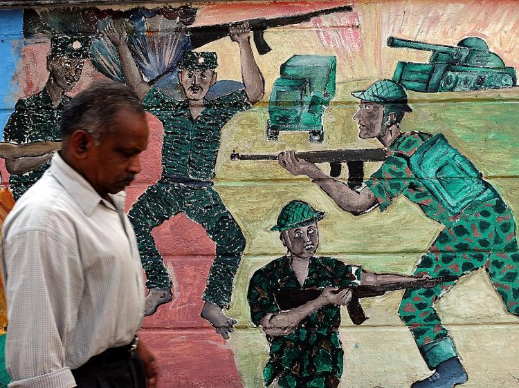 WAR CRIMES: A Sri Lankan man walks past a painting on a wall depicting the recent war between the Sri Lankan army and the Liberation Tigers of Tamil Eelam (LTTE) in Colombo. (Indranil Mukherjee/AFP/Getty Images)