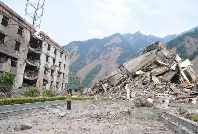 A woman documents the remains of a demolished school in the devastated town of Yingxiu in southwest China's quake-stricken Sichuan province. (Frederic J. Brown/AFP/Getty Images)