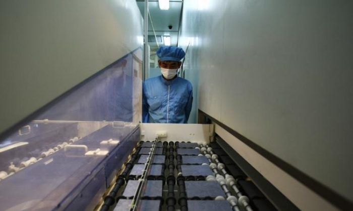 A worker controls the production line of the silicon chips which used for making photoelectric board product at the plant of Tianwei Yingli Green Energy Resources Co., Ltd on June 24, 2009 in Baoding, China. (Feng Li/Getty Images)