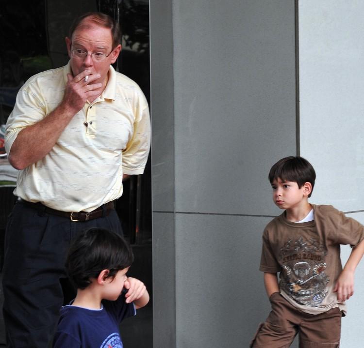A man smokes a cigarette by children