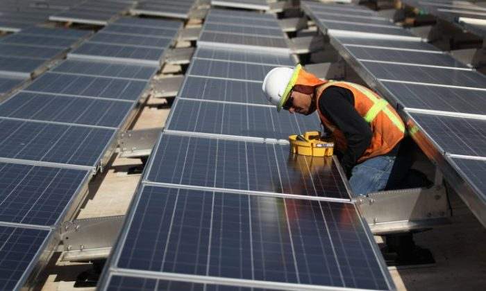 A worker finishes installing solar panels funded by federal stimulus funds atop a government building in Lakewood, Colorado in this file photo. (John Moore/Getty Images)