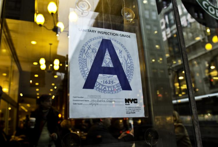 MAKING THE GRADE: A Starbucks coffee shop proudly displays their health inspection grade. Of the restaurants the City has so far graded, 57.2 percent have received an A grade.  (Phoebe Zheng/The Epoch Times)
