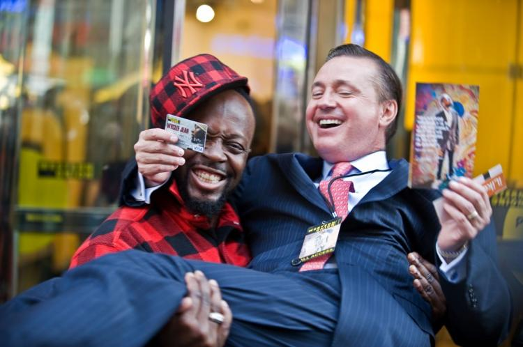 WYCLEF LOVE: Hip-hop artist Wyclef Jean holds Western Union Exec. Stewart A. Stockdale at a promotion for the company's new gift card in Times Square. (Aloysio Santos/The Epoch Times)