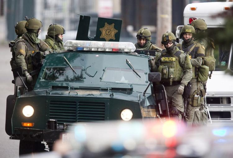 SWAT team members ride on a armored vehicle while searching for a suspect November 29, 2009 near Lakewood, Washington.  (Stephen Brashear/Getty Images)
