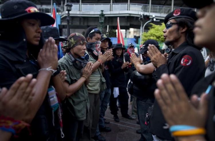 Anti-government Black Shirt Guards pray at a shrine on May 13 in central Bangkok. The Black Shirt Guards are used as security forces for the anti-government 'red shirt' protesters. Anti-government leader and military adviser Major-General Khattiya Sawasdi (Paula Bronstein /Getty Images)