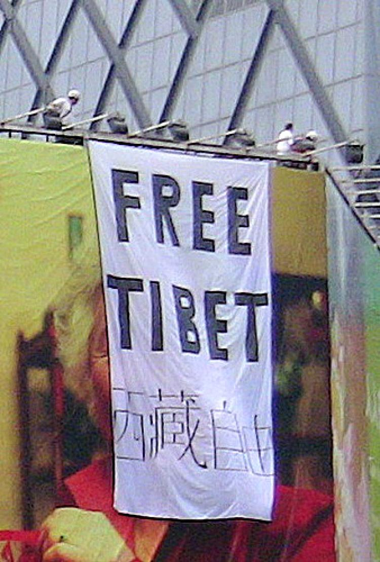 Members of Students for a Free Tibet group hang banner over Olympic Games billboard in Beijing.  (Courtesy of Students for a Free Tibet)