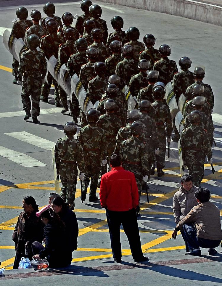 Residents look at Chinese soldiers as they patrol in Kangding county, the capital of Ganzi Tibetan Autonomous Prefecture, in China's southwestern Sichuan province on March 23, 2008.  (Teh Eng Koon/AFP/Getty Images)