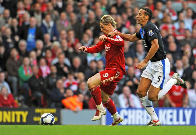 Liverpool's Fernando Torres (left) pulls away from Manchester United's Rio Ferdinand to score the game's opening goal. (Paul Ellis/AFP/Getty Images)