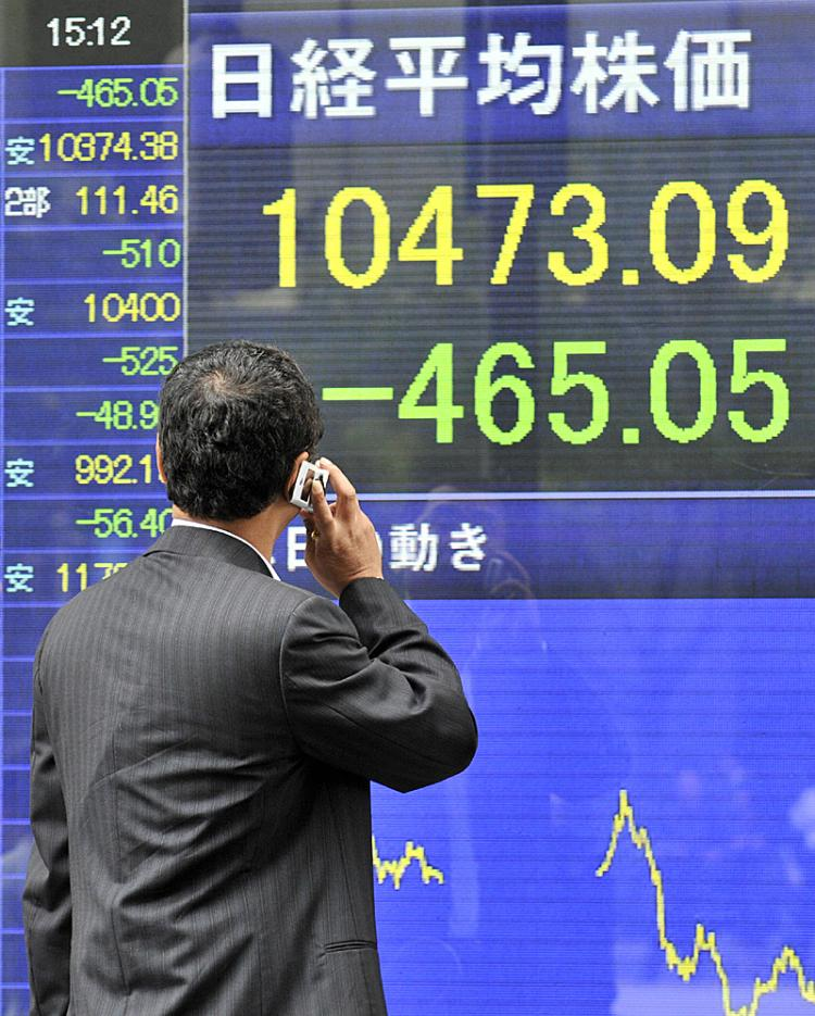 A businessman gazes at a share prices board in Tokyo showing share prices plummeting.  (Yoshikazu Tsuno/AFP/Getty Images)