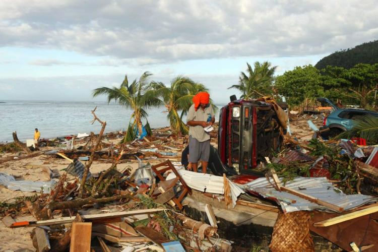 A Samoan man searches amongst the debris at the beach following an 8.3 on the Richter scale strong earthquake which struck on September 30 in Lalomanu, Samoa. (Phil Walter/Getty Images)