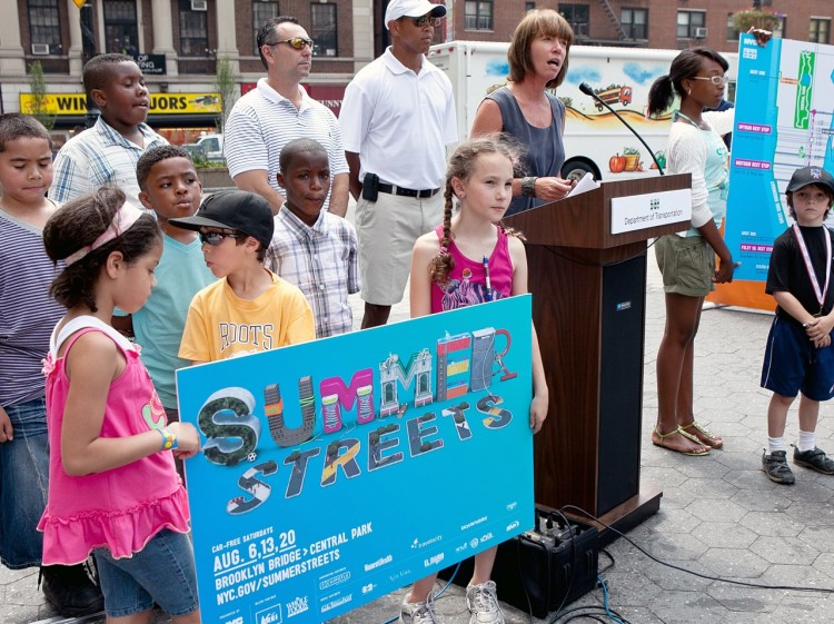 SUMMER STREETS: Young children hold a sign for the Summer Streets initiative, while Department of Commissioner Janette Sadik-Khan speaks and former sports stars John Starks and John Franco look on. (Amal Chen/The Epoch Times)