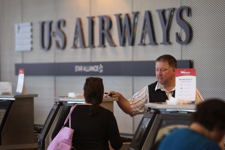 In this file photo, a passenger checks in for a flight at the U.S. Airways counter at O'Hare Airport in Chicago, Illinois. The airline announced that it would cut 1,000 jobs and focus on some core routes as it struggles to return to profitability. (Scott Olson/Getty Images)