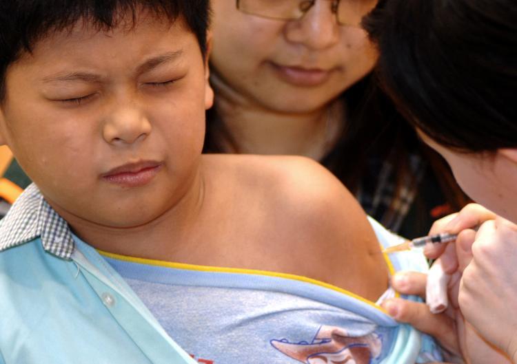 FLU JAB: A boy receives an injection of swine flu vaccine.