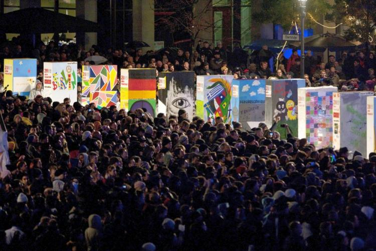 Spectators watch as giant, painted styrofoam dominoes stand along the route of the former Berlin Wall near the Brandenburg Gate on November 9, 2009 in Berlin, Germany. (Henning Schacht-Pool/Getty Images)