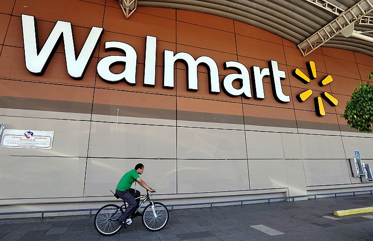 A man rides his bike past a Walmart store in Mexico City, Mexico