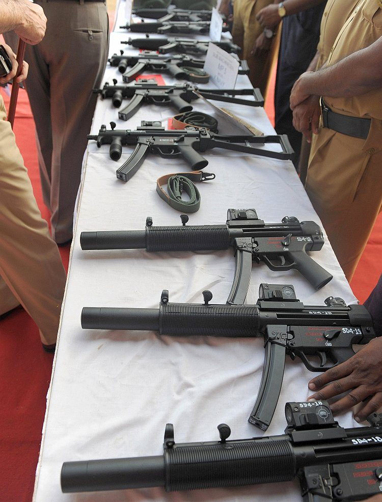 Indian policemen inspect various imported automatic weapons
