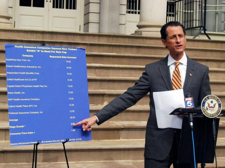 INSURANCE TRACKER: Rep. Anthony Weiner refers to a chart that compares high health insurance companies' rate increase requests and much lower wage increases at a press conference at City Hall on Sunday. (Catherine Yang/The Epoch Times)