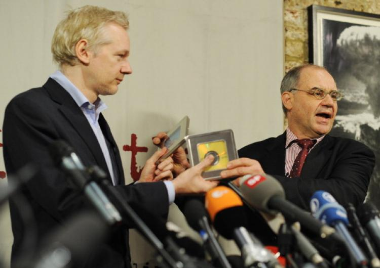 Former Swiss banker Rudolf Elmer (R) gives WikiLeaks founder Julian Assange (L) two CDs following a press conference in London, on January 17, 2011.  (Ben Stansall/AFP/Getty Images)