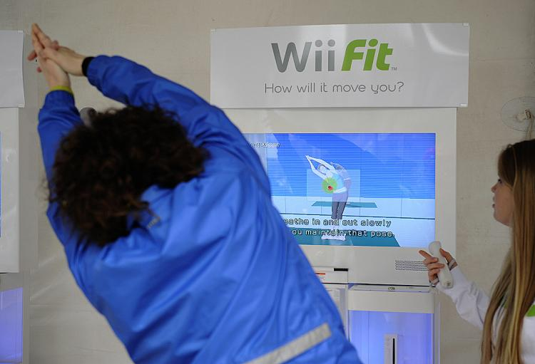 A woman tries the Wii Fit, Nintendo's latest extension to its popular Wii game console, during an event to mark the Wii Fit launch in New York, May 19, 2008.    (Emmanuel Dunand/AFP/Getty Images)